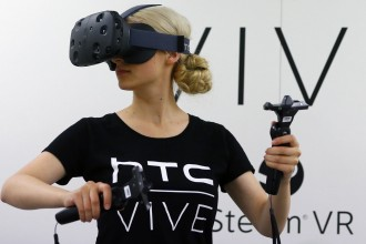 A woman checks a pair of Vive Virtual Reality goggles, produced by Taiwan's HTC, during the Gamescom 2015 fair in Cologne, Germany August 5, 2015. The Gamescom convention, Europe's largest video games trade fair, runs from August 5 to August 9. REUTERS/Kai Pfaffenbach  - RTX1N5FQ